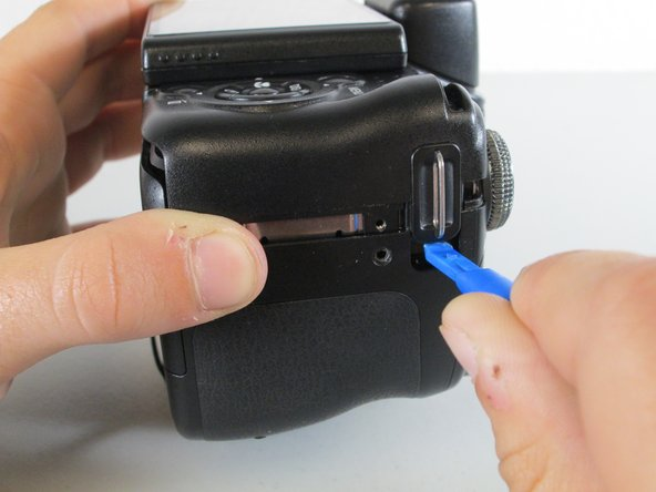 Place the camera on its lens and use the plastic opening tool to pry at the crack in the case on all four sides of the camera.