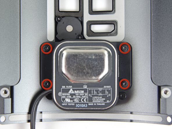 Remove the four 6.5 mm T4 screws (with washers) from the flange around the AC socket.