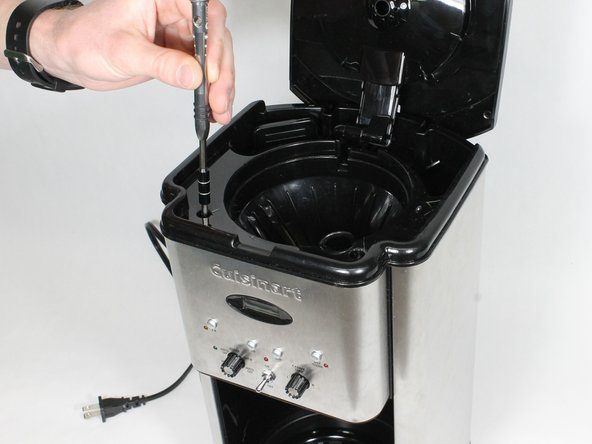 Remove the two 11 mm long screws from the top of the coffee maker underneath the cover using the bit driver with the extension with the PH1 Phillips bit.