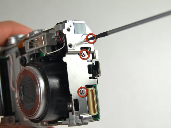Image 2/3: Remove the screw by the shutter button.