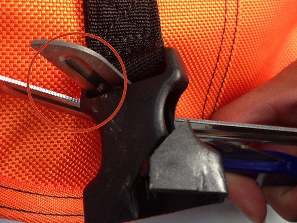 Using scissors (preferably industrial scissors), cut buckle off and remove buckle from fabric loop.