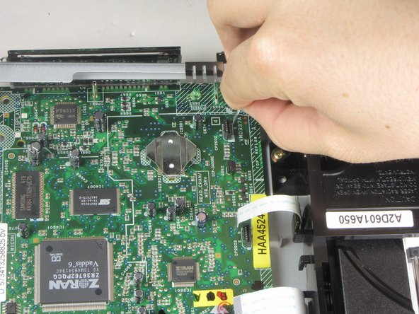 Remove the thrid of three ribbon cables on the left hand side of the disc drive by pulling vertically.