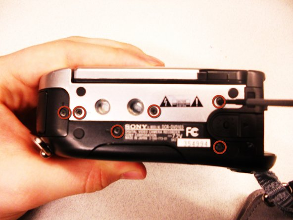 Remove the (6) 4.5mm screws from the bottom of the Sony Handycam that are marked with small circles.
