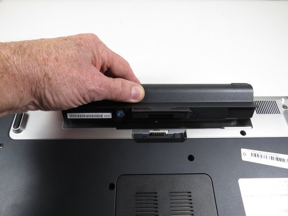 "While holding the ""Release"" switch toward the center of the computer, press on the raised portion of the battery pack away from you. The battery  pack will pop up."