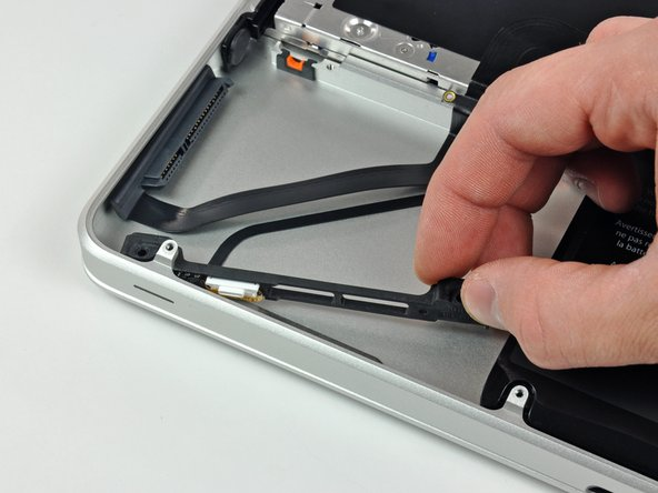 Image 1/2: Carefully peel the hard drive and IR sensor cable from the upper case.