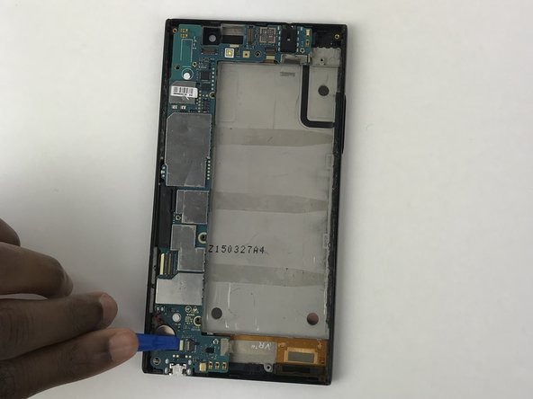 Unclip the motherboard from the phone with the plastic opening tool.