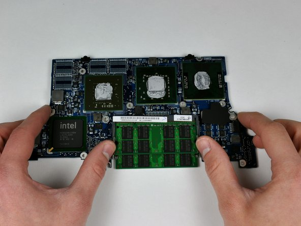 "Release the tabs on each side of the RAM chip at the same time. These tabs lock the chip in place and releasing them will cause the chip to ""pop"" up."