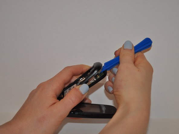 Using the plastic opening tool, gently pry open the back piece of the phone.