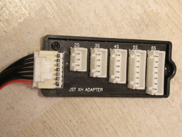 Press down on the tab located on the top of the white molex connector and firmly pull away from the charger body.