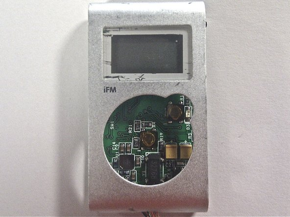 Carefully remove the circuit board/LCD component from the device by pulling it towards the left open panel.