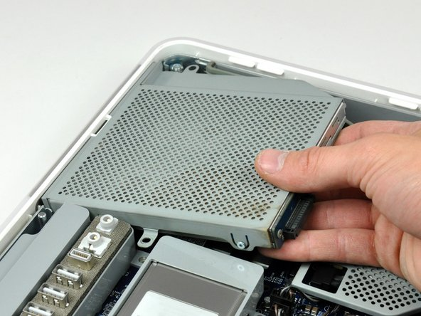 Image 2/3: Lift the free end of the optical drive slightly, then pull it away from the edge of the rear case to clear the two plastic positioning pins.