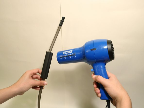 Using a hair dryer, apply heat to shrink the tube until it is tightly sealed in place.