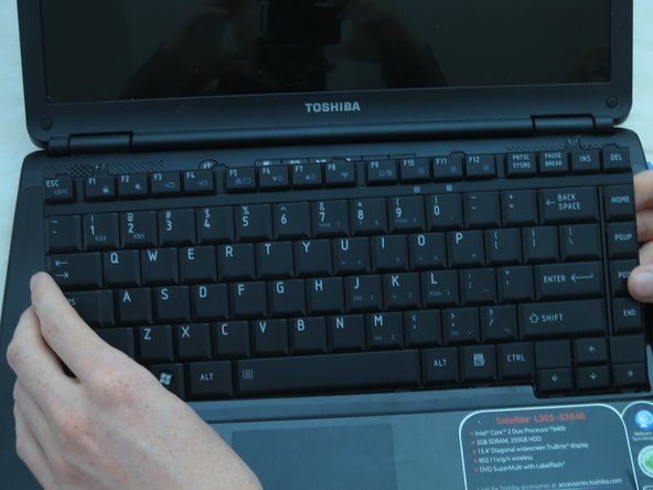 Gently grasp the top of the keyboard. Pull it up and toward the screen.