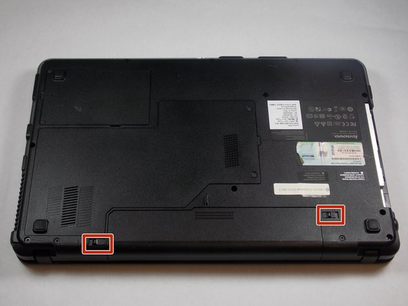 Locate the switches on the bottom of the computer on either side of the battery, as shown in the picture.