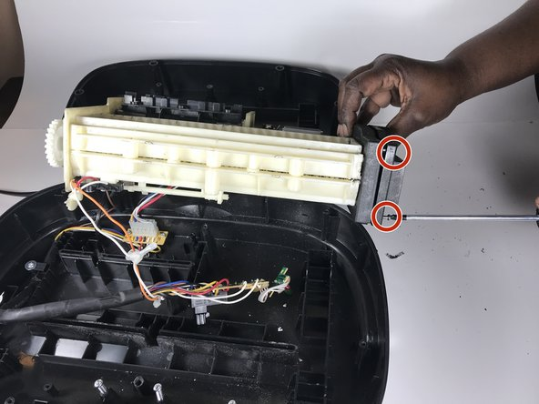 Remove screws from the gear box cover on the right side with a Phillips screwdriver. The screws are identified by the two marked circles. The screws are 7 mm in length and the head diameter is 3 mm.