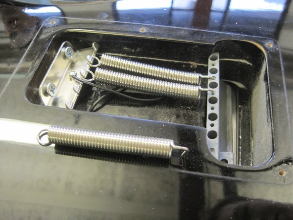 Remove the three tremolo springs from the spring claw and tremolo block.