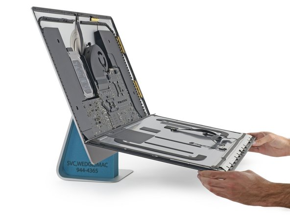 Image 3/3: With the adhesive tape gone, we get our first peek at the hardware inside the Retina 5K iMac.