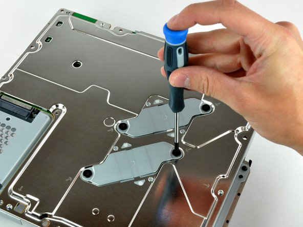 Image 1/2: Unscrewing several screws securing the EMI shield.