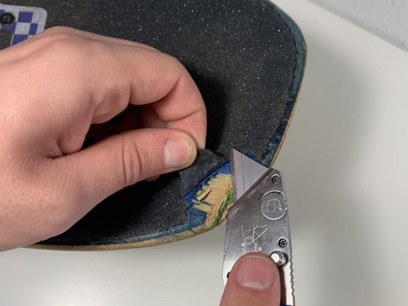 Using an X-Acto knife or a razor,  cut off any excess grip tape that is not sticking to the board.