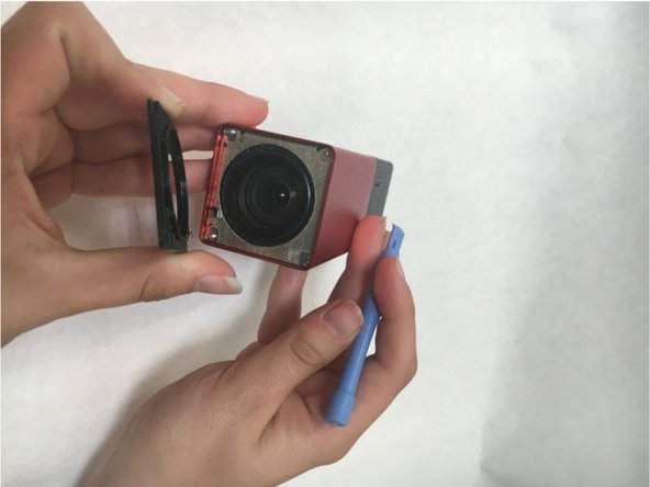 Remove the lens covering by using the plastic opening tool to pry it away from the camera. There are strong magnets attached to the bottom so some force is required.