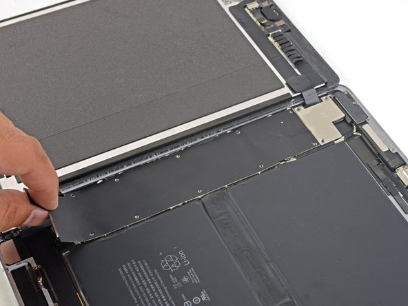 Lift the logic board EMI shield, starting at the edge nearest the top of the iPad.