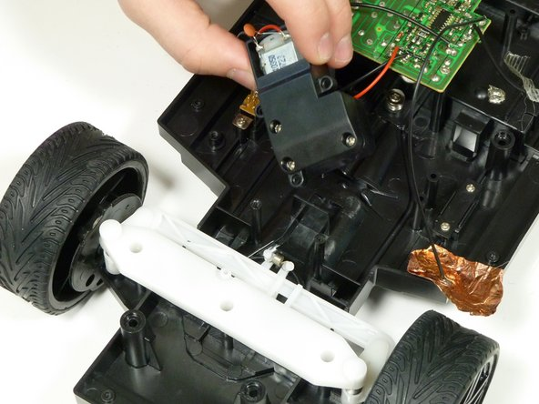 Remove the front motor and its casing from the chassis of the car.