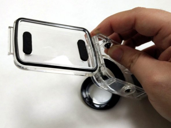 Apply pressure to the lens cover with your thumb, and use your other fingers to pull up on the case, separating the lens and lens trim from the case.