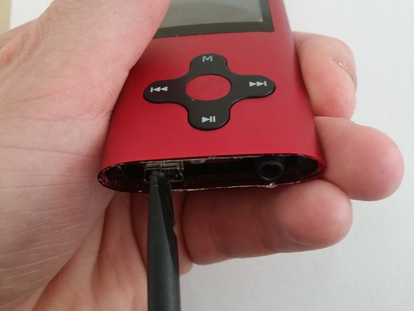 Use the spudger to push the USB port on the bottom of the device inward.
