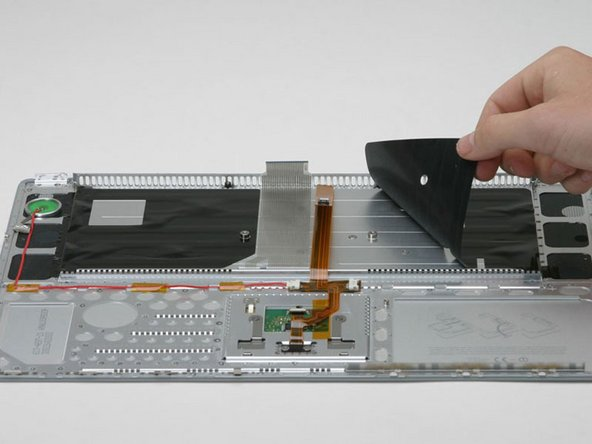 Image 1/1: Peel back the black plastic shielding on either side of the keyboard (there are two pieces).