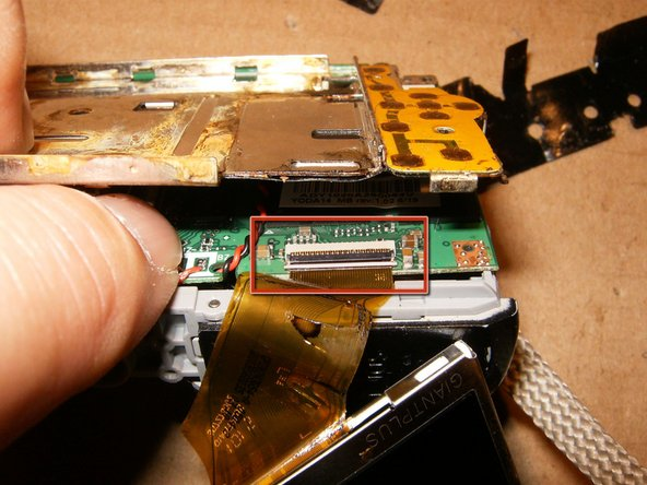 Lift the LCD frame slightly up and fold the black clip gently to the back.