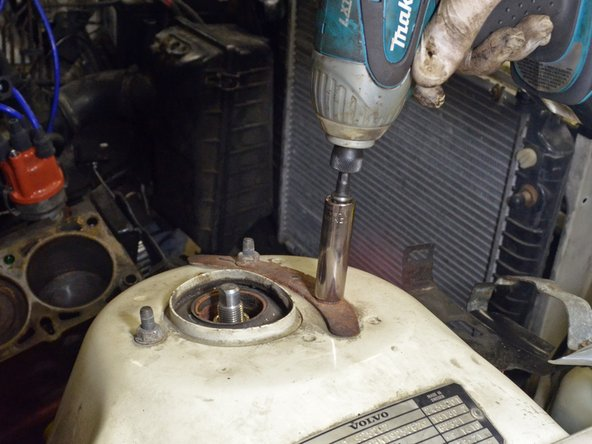 Image 2/3: Use a ratcheting socket wrench or impact wrench with a 13 mm deep socket to remove the three nuts.