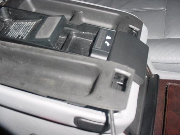 Once the center console is out, remove the two parcel trays inside the arm rest containers by gently lifting up from the front side first.