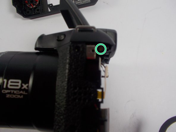 Image 2/3: Remove the two screws placed on the right and left sides of the camera.