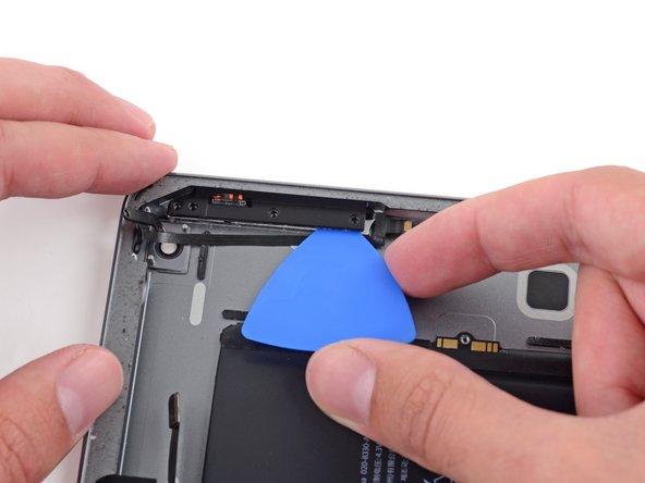 Image 2/2: Slide the pick around the corner to loosen the adhesive—but do not cut any further, or you may damage the button cables.