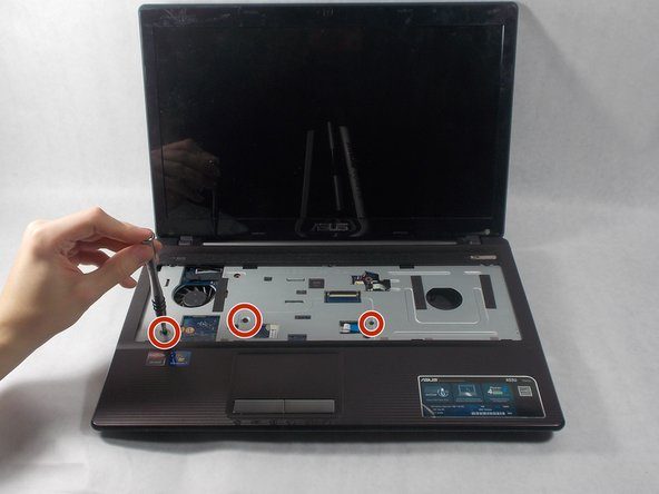 Flip the laptop over again, open it, and unscrew the three 7mm screws using a Phillips #1 screwdriver.