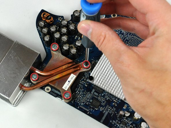 It may be necessary to hold the Phillips head screw sockets with a Phillips screwdriver while unscrewing the four Torx screws near the corners of the processor.