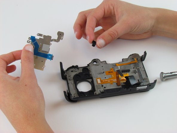 Use your fingers to remove the metal piece with the blue ribbon cable and the rubber buttons lying underneath.