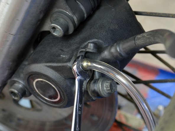 "Using a 3/8"" wrench with your left hand, open the bleed valve on the front brake cylinder."
