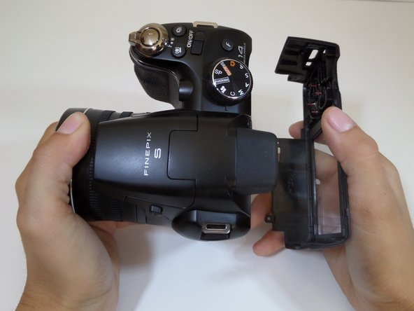 Use force to pull apart the back casing from the camera.
