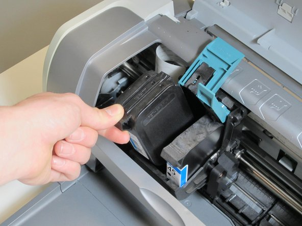 Remove the color ink cartridge by lifting back the teal plastic cover located on top of the cartridge.  Proceed by repeating this step from the black ink cartridge.  Then grab the pertruding part on the top of the cartridge, and lift cartridges gently out.