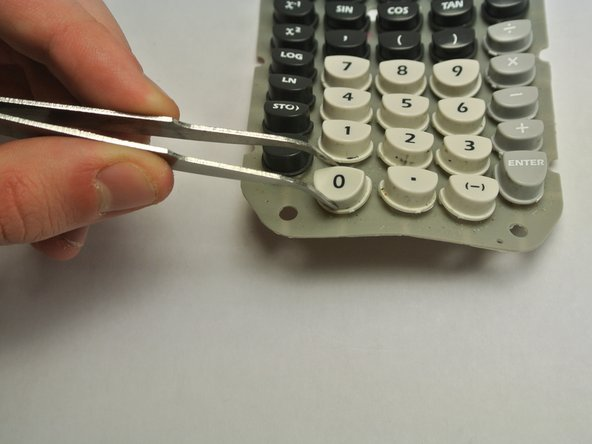Place the tweezers around the key.