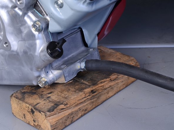 Place the engine on your work surface and prop up the rear by placing a wooden block underneath it.