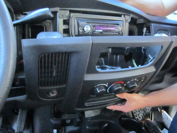 Grasp the bottom right hand corner of the console trim and slowly pull toward you.  Gradually increase your force until the you feel the right side clips pop off.