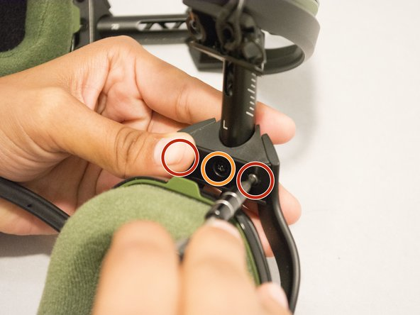 Use a screwdriver with a T9 bit to remove one screw from the lower headband plate.