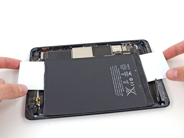 Grasp both cards and slowly pull the right side of the battery up about two inches from the rear case.