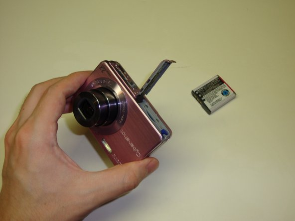 Image 1/3: To begin, power the camera on so that the lens extends fully.  While the lens is extended, eject the battery as described in step one.  Otherwise, the camera will retract the lens.