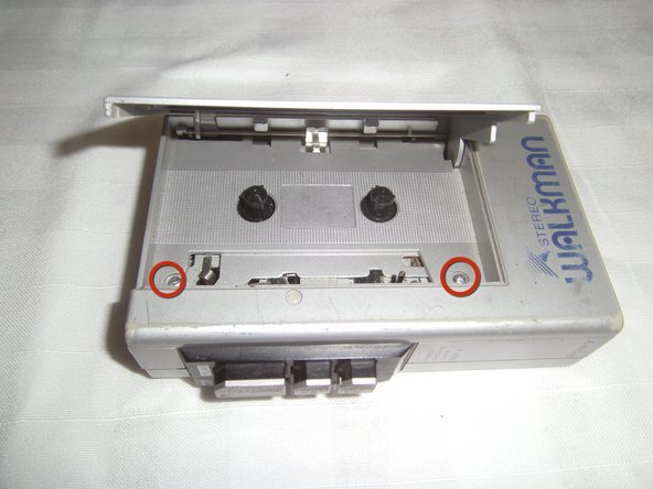 Turn over your Walkman and gently press the cover to open the cassette holder.