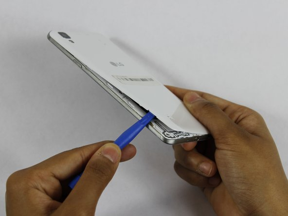 Insert a fingernail, or plastic opening tool, into the cutout on the back cover and pry outward to remove.