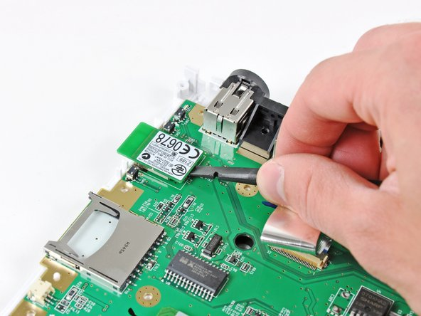Use the flat end of a spudger or your fingertips to lift up the end of the Bluetooth board nearest the center of the motherboard.