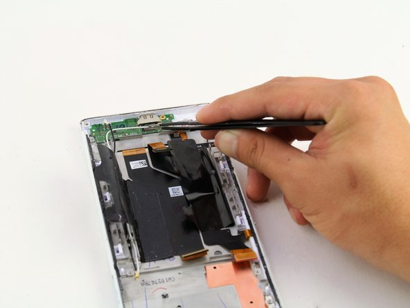 Grab the white wire connected to the charging port PCB board using your flathead tweezers.